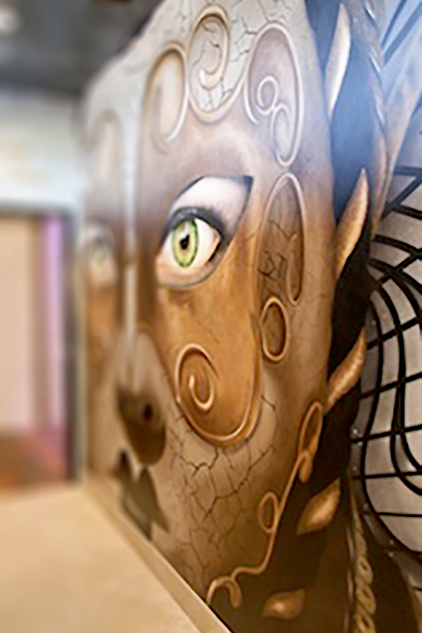 Mural of a theatrical face mask on the entrance lobby of a Houston Theater designed by Shundra Harris Interiors