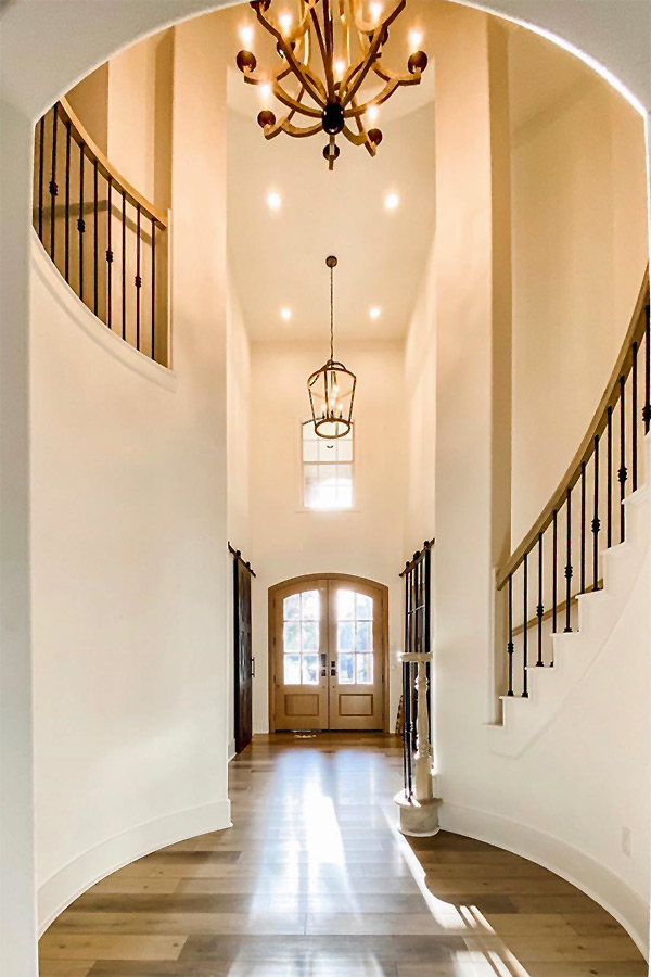 Entrance of a multistory home with large double door and stair curving staircase