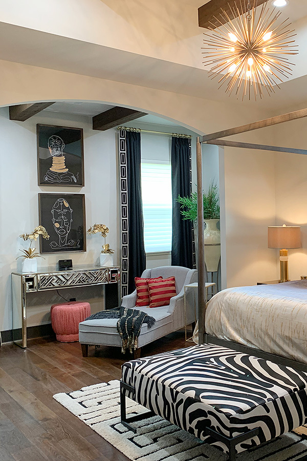 Bedroom with a zebra printed bench and matching console table and dark curtains lined with ethnic borders.