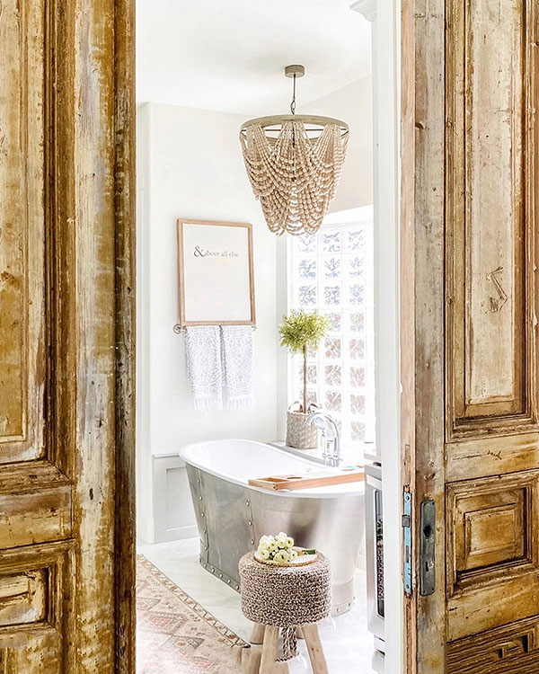bathroom renovation in white with beaded chandelier, wall art, and antique wooden sliding doors at entry