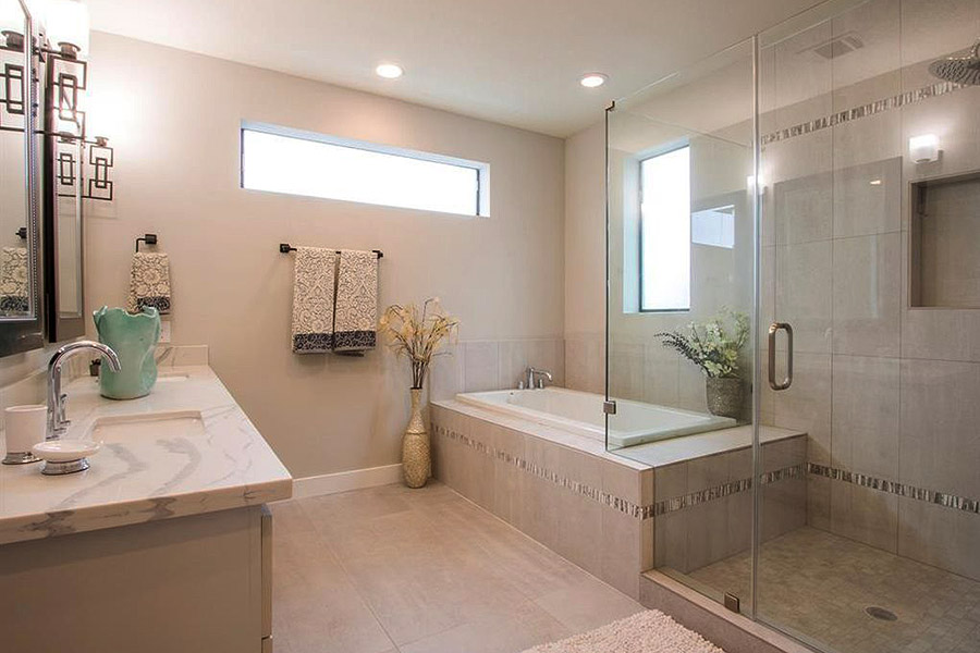 large master bath with beige marble floors, sink counter and bath tub and a panoramic window over the tub