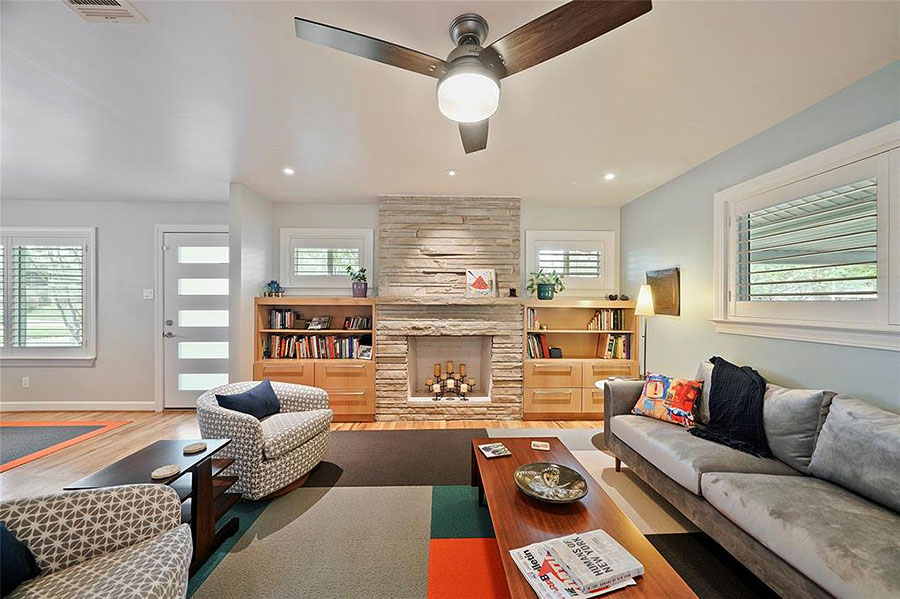 Living room with built in shelves set up in midcentury modern style furniture and colors
