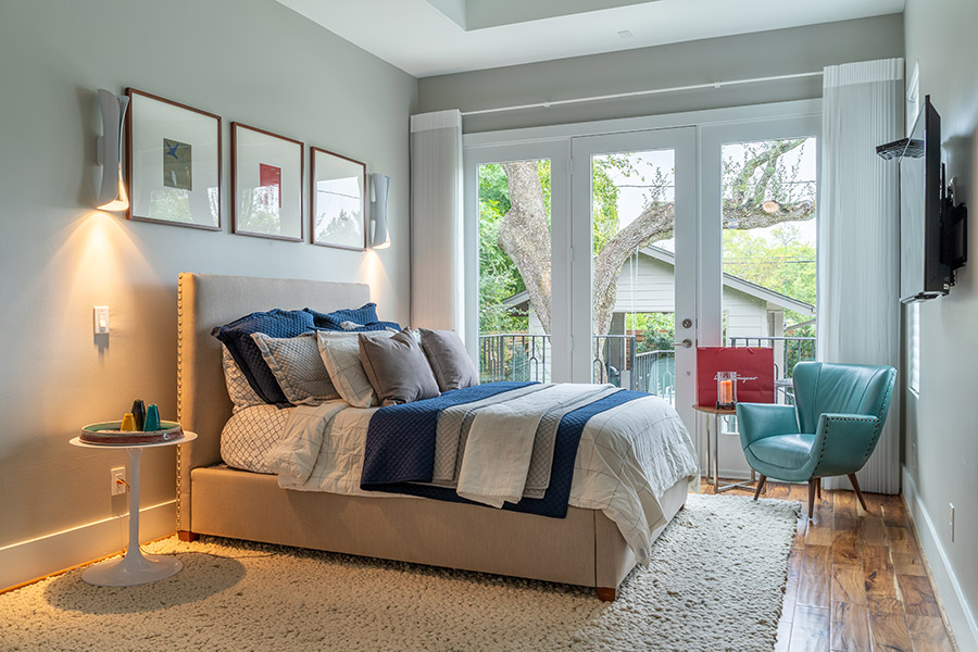 bedroom with ceiling to floor windows and door leading to a courtyard furnished with modern platform bed in blues and whites.