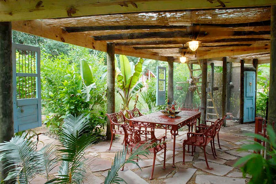 Covered outdoor dining area with wooden pergola and lighting.