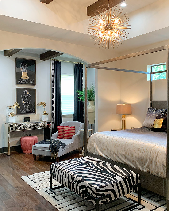 bedroom with four poster bed and black and white zebra inspired furniture