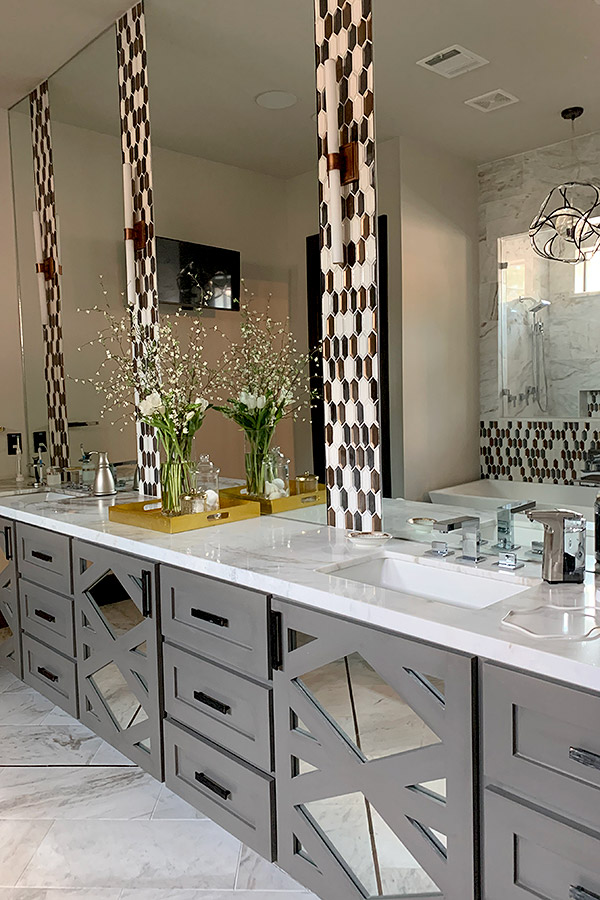 bathroom with double vanity, white marble countertops with honeycomb backsplashes in brown and white