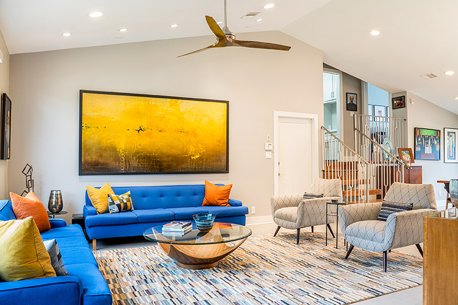 Living room with bright blue sofas and orange and yellow cushions