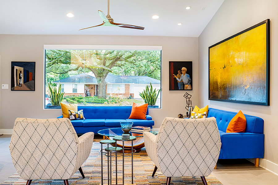 Living room with bright blue sofa and beige chairs