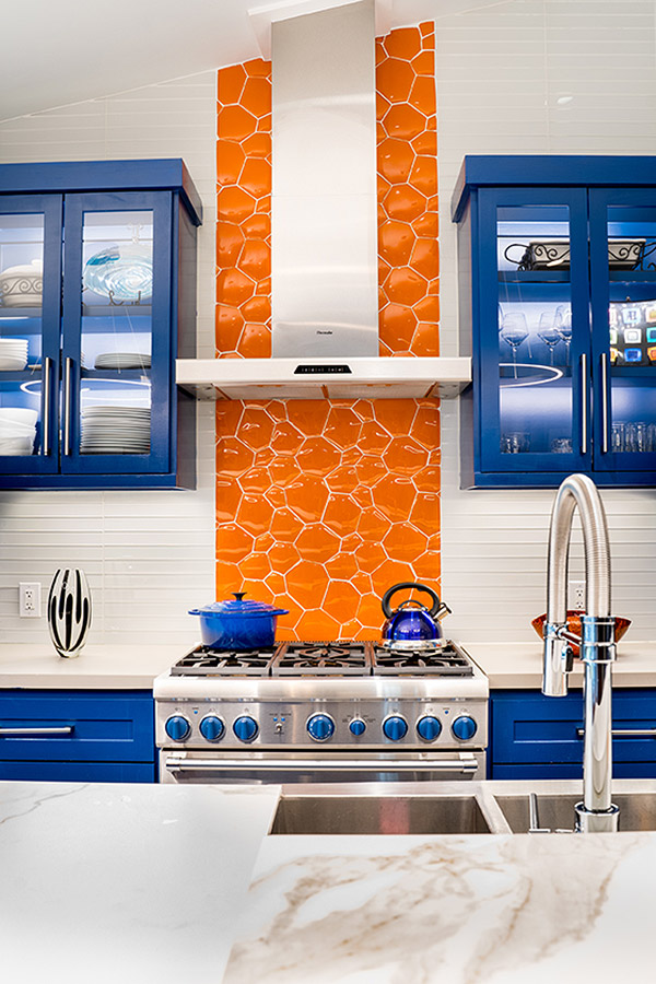 Kitchen with bright blue cabinets and orange back splash behind the stove.