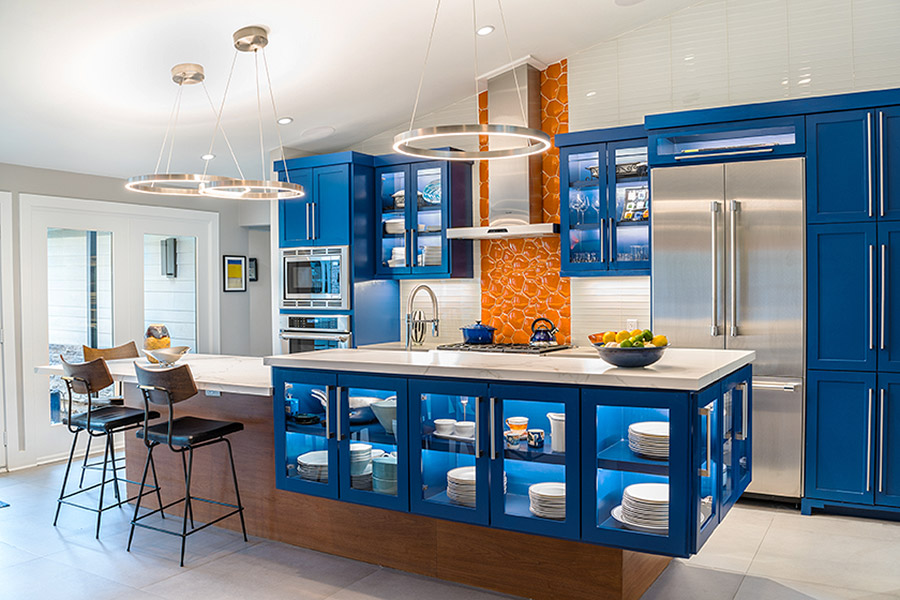Kitchen counter with glass pane cabinets and bar stools