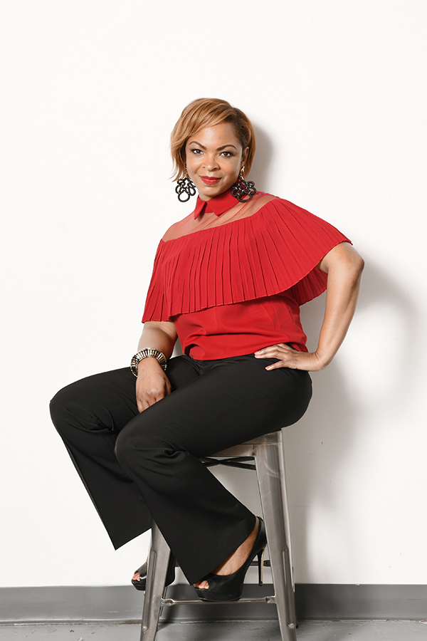 Owner Shundra Harris sitting on a stool with a bold red blouse and black pants.