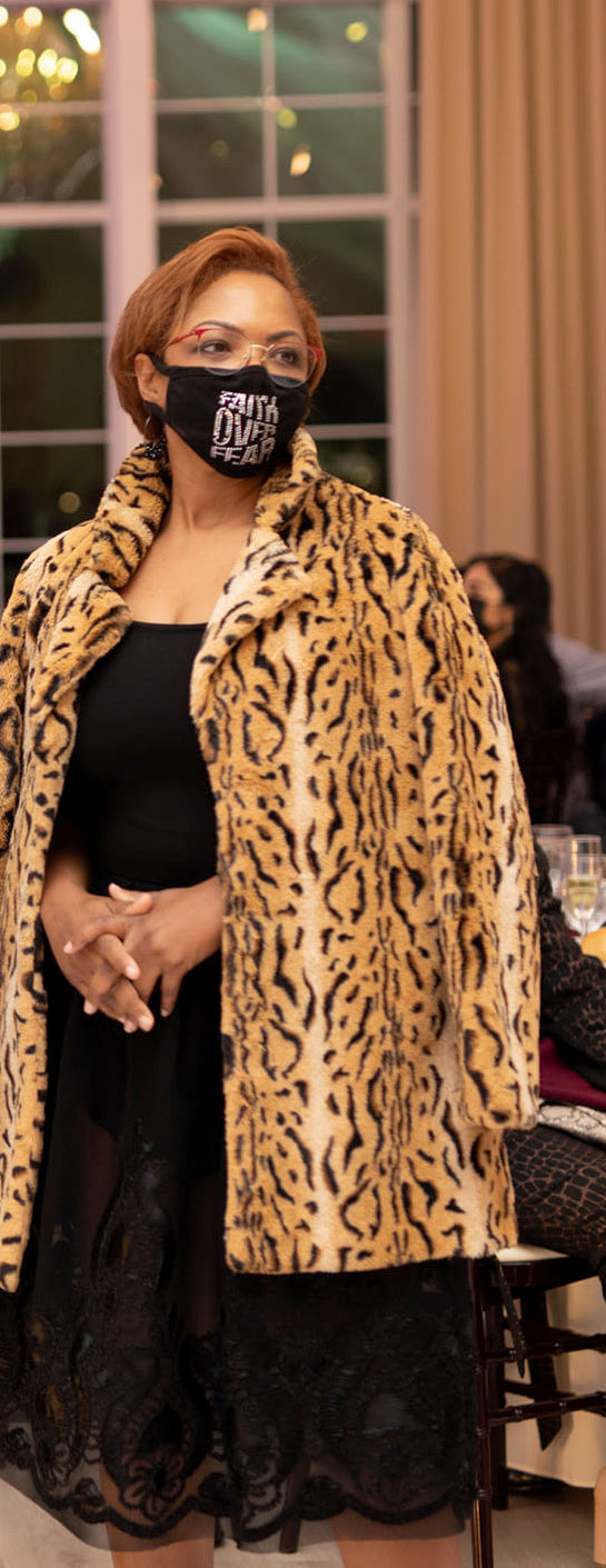 Shundra Harris with mask over her mouth at a speaking event wearing black cocktail dress with a leopard print coat draped over her shoulders.