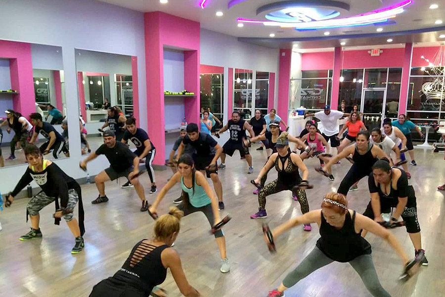 people working out in a group class at the Cinthia's fitness center with pink walls and ambient lighting.
