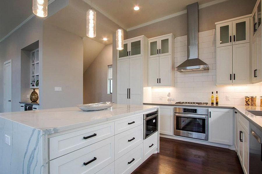 Kitchen in white marble and white cabinets with stainless steel fixtures