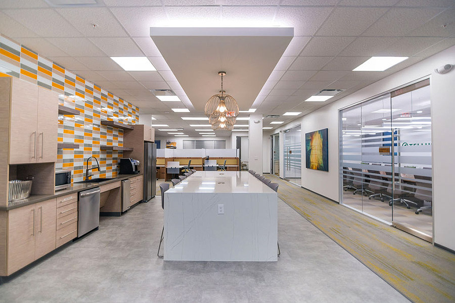 Cafe area in an office building with modern decor in white and yellow, orange, and beige colors