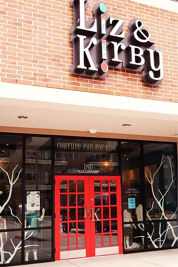 store front designed by Shundra Harris Interiors showing signage in serif font for Liz and Kirby children clothing store with double door with window panes in red color