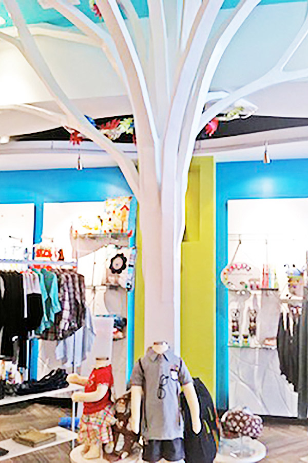 a tree camouflage structure painted in white that conceals the beam in the middle of the store