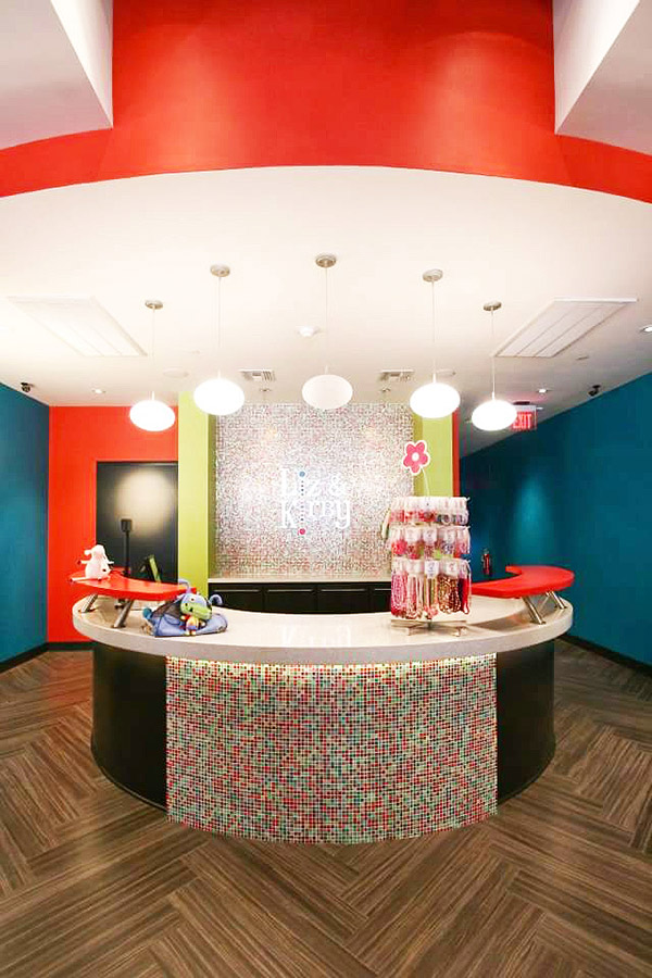 Check out desk at the children's store in a colorful theme of red, white and lime green with mosaic tiles covering the front of the counter