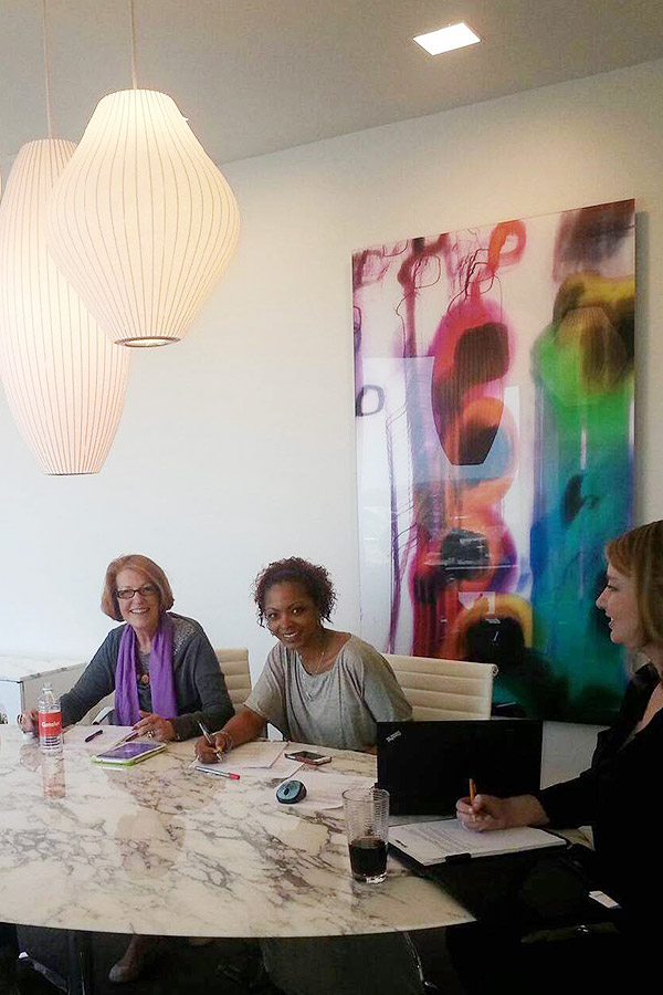 Shundra Harris sitting at a table with other 3 other women and large colorful painting on the wall behind them