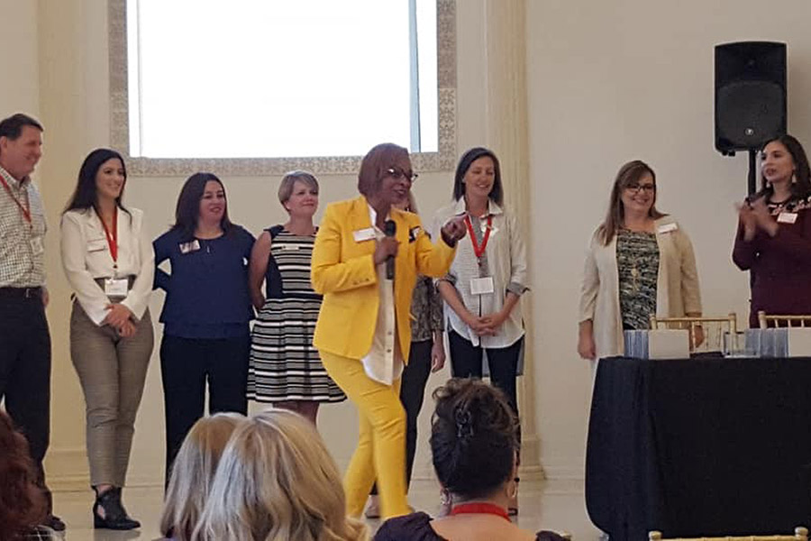 Shundra harris dressed in yellow suit at a symposium