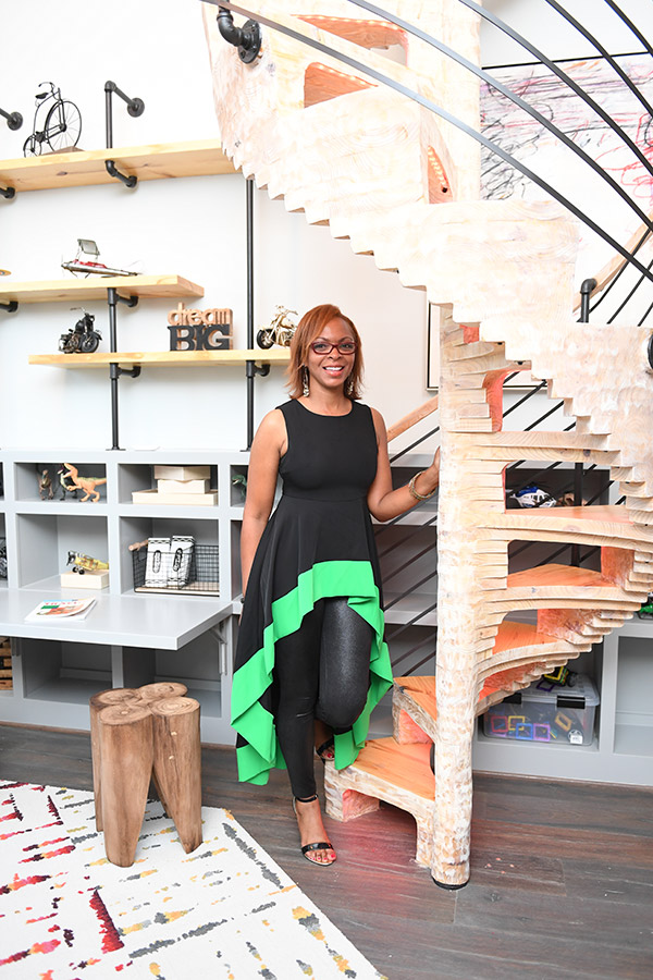Shundra Harris stands in a black dress with green trim against a spiral staircase custom designed for a child's room in a show house interior