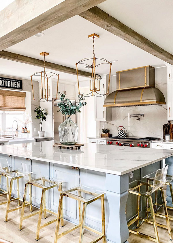 kitchen island with white marble top and gold framed bar stools