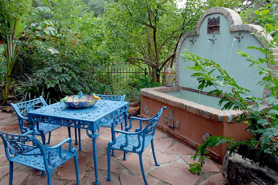Patio furniture painted in blue set next to a water fountain in a paved courtyard.