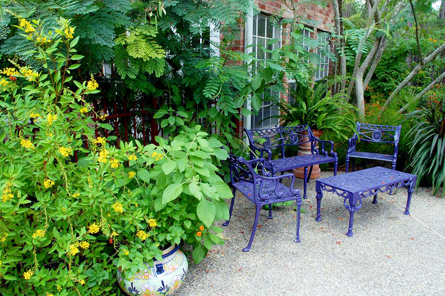 Out door seating with purple painted metal chairs and table against a full green foliage planted in pots and in the ground