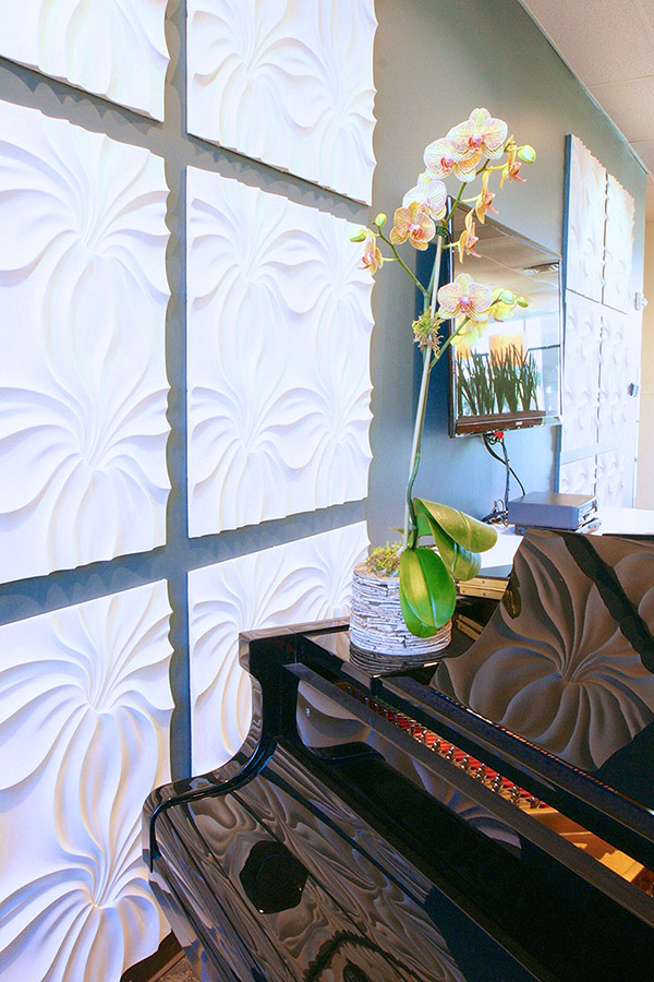 a piano in a lobby against a wall with white textured tiles