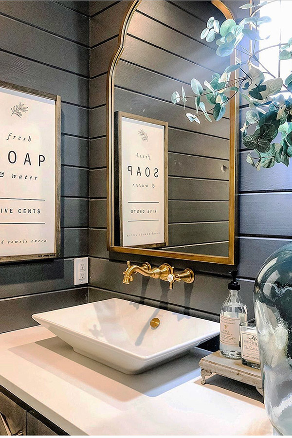 bathroom vanity with a rectangular sink and golden faucets. A mirror hangs on slated wall painted in dark brown.